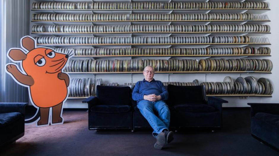 Armin Maiwald, Filmemacher, Autor und Miterfinder der Sendung mit der Maus sitzt auf einem Sofa in seinem Büro vor zahlreichen Filmrollen.