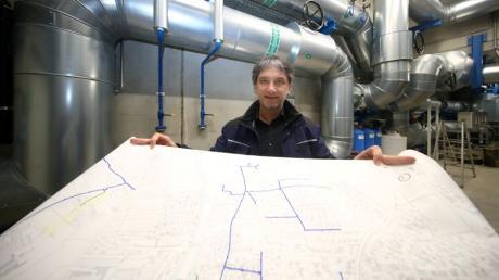 Geschäftsführer Markus Hertel steht mit einem großen Plan des Weißenhorner Fernwärmenetzes im Pumpenhaus beim Müllheizkraftwerk.