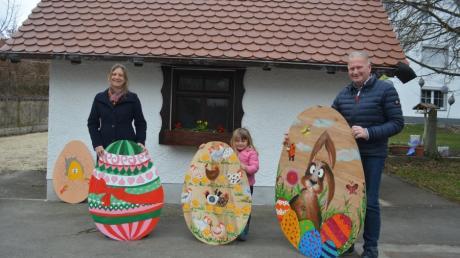 Die Vereinsgemeinschaft Wullenstetten organisiert eine Ostereiersuche. Auf dem Bild sind Andrea Zosel (links), Josef Ölberger und die vierjährige Magdalena mit drei der von Freiwilligen gestalteten Eiern zu sehen.