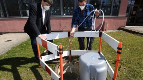 Meitingens Bürgermeister Michael Higl (links) beobachtet, wie Abwassermeister Norbert Uhl eine Probe zieht, die dann auf Coronaviren untersucht wird.