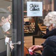 """Eine Kundin kauft bei der Parfümerie Naegele in Augsburg per """"Click & Collect"""" ein. Die Verwirrung der Kunden sei angesichts der sich ständig ändernden Regeln groß, berichten Händler."""