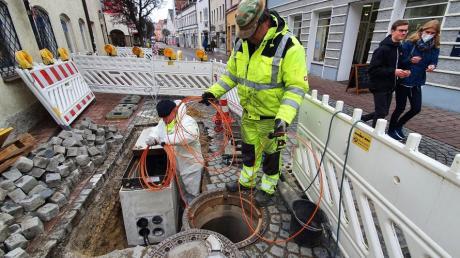 Facharbeiter verlegen Glasfaserkabel unter der Rosenstraße. In der engen Kanalisation hilft ihnen ein Roboter dabei.