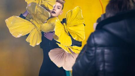 Ana muss beim Fotoshooting mit überdimensionalen Schmetterlingen posieren.