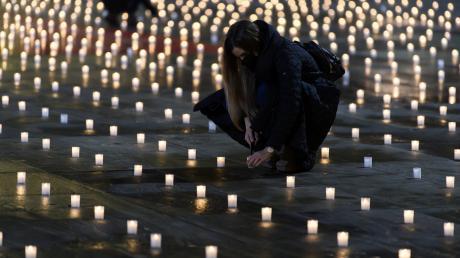 Aktivisten zünden knapp 5000 Kerzen an, um der Menschen zu gedenken, die am Coronavirus gestorben sind.
