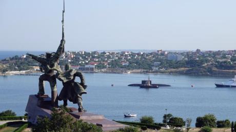 Hinter einem sowjetischen Denkmal liegen ein U-Boot und Kriegsschiffe der russischen Schwarzmeerflotte vor Anker in der Hafenstadt Sewastopol. (Archivbild).