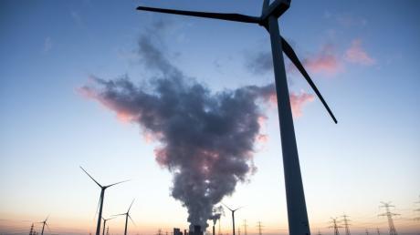 Vorne das dreht sich das Windrad, im Hintergrund arbeitete das Braunkohlekraftwerk. Die EU-Kommission setzt auf erneuerbare Energie, um das Klima zu retten.