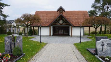 Auf dem Friedhof in Todtenweis werden nun neben Urnenstelen (links) auch Erdgräber für Urnen angeboten. Sie sollen östlich der Aussegnungshalle (rechts) entstehen.