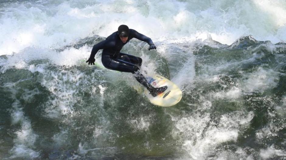 Ein Surfer surft auf der Eisbachwelle im Englischen Garten. Auch wenn alles so locker und offen wirkt: Die berühmte Münchner Welle darf längst nicht jeder reiten.