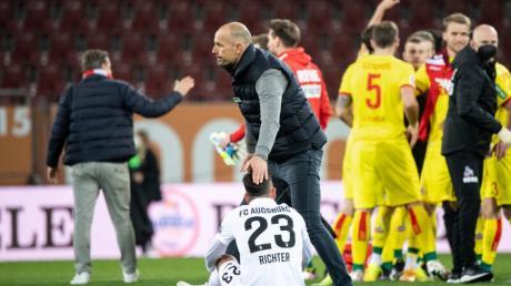 Nach der Niederlage gegen Köln tröstete Trainer Heiko Herrlich (oben) seine Spieler. Ob er als Trainer des FC Augsburg weitermachen darf, ist noch offen.