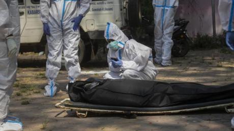 Die Verlobte eines an den Folgen einer Corona-Infektion Verstorbenen kniet vor der Einäscherung in Gauhati neben dem Leichnam. In Indien sind seit Pandemiebeginn insgesamt mehr als 200.000 Menschen in Verbindung mit dem Coronavirus gestorben.