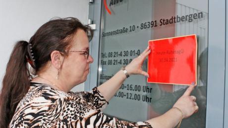 """Monika Geiger bringt das Schild an: """"Heute Ruhetag"""" steht darauf, denn am 30. April hat die Geschäftsstelle der AWO Schwaben in Stadtbergen geschlossen. Grund hierfür ist ein spezieller Ruhetag."""