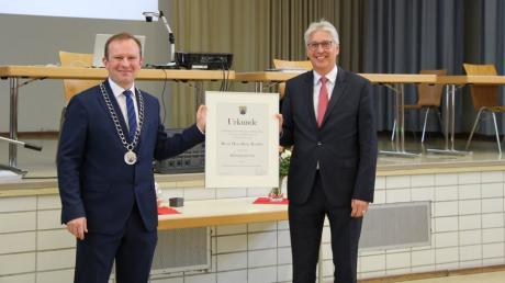 Bürgermeister Florian Mayer (links) verleiht seinem Vorgänger Hans-Dieter Kandler die Altbürgermeisterwürde sowie den goldenen Ehrenring des Marktes Mering.