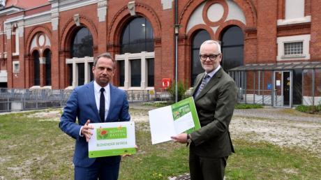 """Vor dem historischen Kraftwerksgebäude in Langweid überreichte Minister Thorsten Glauber (links) die Urkunde """"Blühender Betrieb"""" an LEW-Vorstandsmitglied Markus Litpher."""