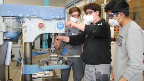 Emil Reichert, Azubi bei MLB, zeigt David Müller und Mansour Arab aus der Praxisklasse der Mittelschule Bobingen, wie die Bohrmaschine funktioniert.