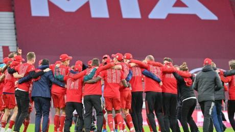 Bayerns Spieler feiern nach Spielende die Deutsche Meisterschaft auf dem Rasen der leeren Allianz Arena.