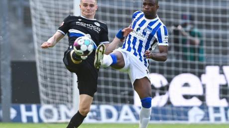 Bielefelds Amos Pieper und Herthas Jhon Cordoba (r) gehen mit gestreckten Beinen zum Ball.