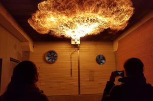 Diese Feuerwalze wird in der Feuerwehrerlebniswelt Augsburg erzeugt. So weit oben an der hohen Decke ist sie für Menschen ungefährlich. Entsteht eine Feuerwalze bei einem echten Brand, ist sie lebensgefährlich.