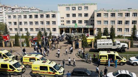 Einsatzkräfte von Polizei und Rettungsdiensten stehen vor einem Gymnasium. Bei einem Angriff auf die Schule sind mehrere Menschen getötet worden.