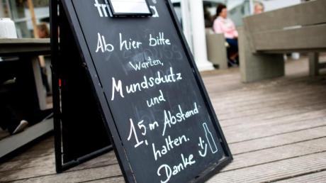«Mundschutz und 1,5 m Abstand halten» steht auf einem Schild vor einem Lokal auf der Nordseeinsel Norderney. Niedersachsen öffnet den Tourismus zunächst nur für die Einwohner des eigenen Bundeslandes.