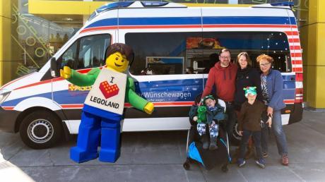Parkmaskottchen Legoland Boy begrüßt den Wünschewagen mit dem acht Jahre alten Jacob und seiner Familie am Eingang.