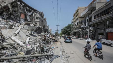 Palästinenser fahren an Gebäuden in Gaza vorbei, die durch israelische Luftangriffe zerstört wurden.