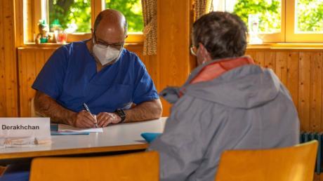In Wulfertshausen gibt es eine Impfaktion. Dr. Arian Derakhchan im Aufklärungsgespräch mit Peter Miller aus Friedberg.