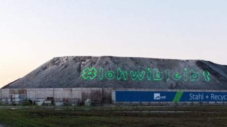 Die Klima-Aktivisten von Wald statt Stahl haben Dienstagabend mit einem Laserbeamer die Schlackeberge der Lech-Stahlwerke in Meitingen angestrahlt, um für den Erhalt des Lohwalds zu demonstrieren.