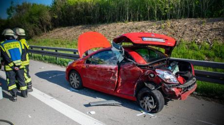 Einsatzkräfte der Feuerwehr stehen am Unfallort neben dem Autowrack.