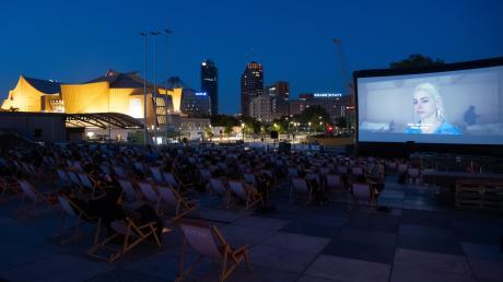Zahlreiche Menschen sitzen am Kulturforum am Potsdamer Platz im Freiluftkino. Das Kino ist eine der Spielstätten bei der diesjährigen Berlinale.