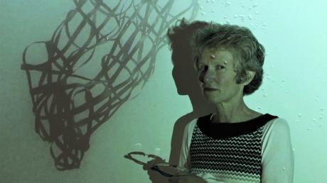 Barbara Ehrmann vor einem ihrer Werke. Der grünliche Farbton stammt von der Beleuchtung ihrer eigenen Videoinstallation.