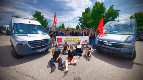 Vier ausgestreckte Finger, vier Prozent mehr Lohn: Die Angestellten von MAN und Daimler treffen sich in Neu-Ulm zu einer Aktion anlässlich der Tarifverhandlungen im Kfz-Gewerbe.