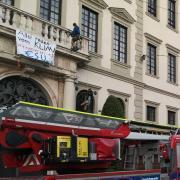 Die Kletteraktion zweier Klimacamp-Aktivisten am Augsburger Rathaus sorgte für einen Einsatz von Polizei und Berufsfeuerwehr.