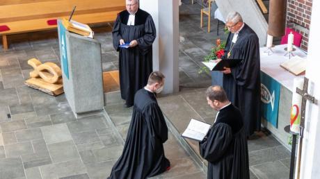 Unter Assistenz durch Pfarrer Leander Sünkel (Lagerlechfeld, links) und Militärpfarrer Markus Linde (Mittenwald, rechts) segnete Militärbischof Bernhard Felmberg Mirko Webler (kniend).