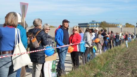 Mit einer Menschenkette protestieren Gegner 2015 gegen den Bau einer Straße durch das Naturschutzgebiet bei Kissing. Auch die reduzierte Planung stößt auf Protest.