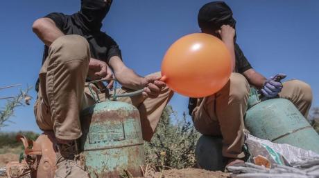 Maskierte Palästinenser präparieren Brandballons.