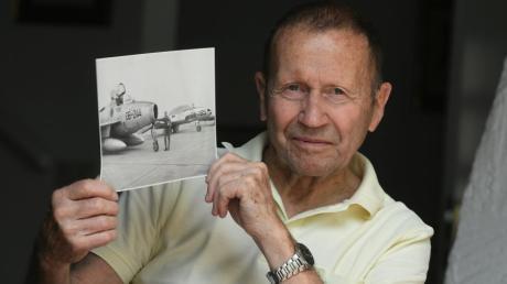 Kampfpilot Friedrich Conrad aus Deuringen mit einem Foto, das ihn vor der DB-244 zeigt, mit der er zu seinem fünften Flug auf dem Lechfeld gestartet war.