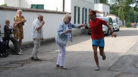 Benedikt Ziegelmeier lief in Fischach seinen ersten Marathon. Die Bewohner des  Altenheims Schloss Elmisschwang reichten ihm Verpflegung.