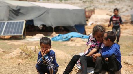 Geflüchtete Kinder sitzen in einem Flüchtlingslager nordwestlich von Aleppo auf einem Stein.