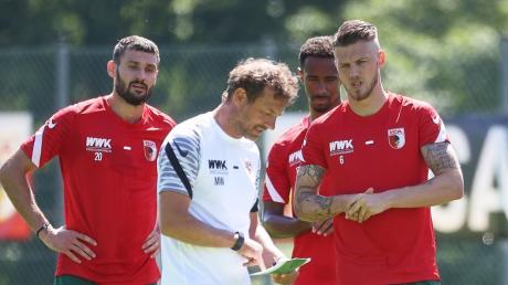 In die Pläne des Trainers eingeweiht: Markus Weinzierl (in Weiß) mit den Mannschaftsräten Daniel Caligiuri (li.) und Jeffrey Gouweleeuw (re.). Im Hintergrund Noah Sarenren Bazee.