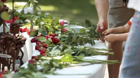 Menschen legen in Oslo Rosen für die Opfer des Terroranschlags nieder.