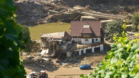 Ein Haus in Marienthal ist nach dem Hochwasser vollkommen aufgerissen, dahinter ist eine zerstörte Brücke zu sehen.