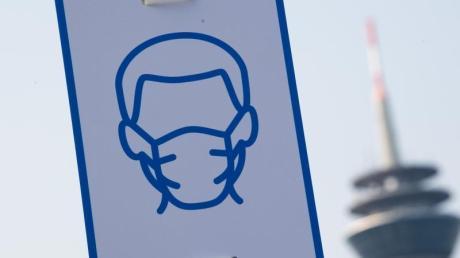 Ein Piktogramm mahnt in Düsseldorf das Einhalten der Maskenpflicht an.