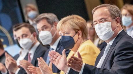 Armin Laschet (rechts), Kanzlerkandidat der Union, sitzt neben Bundeskanzlerin Angela Merkel (CDU) und Markus Söder beim zentralen Wahlkampfauftakt von CDU und CSU.