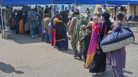 Afghanische Flüchtlinge, die aus Kabul evakuiert wurden, stellen sich nach ihrer Ankunft auf der Air Base Ramstein zur Abfertigung auf.