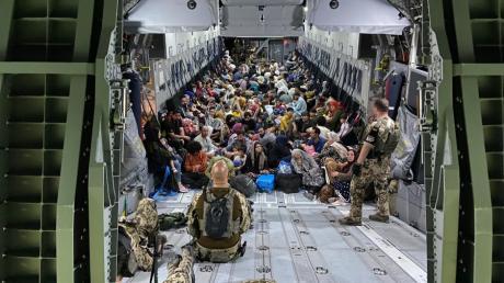 Geflüchtete sitzen in einem Airbus A400M der Bundeswehr. Die Bundeswehr hat deutsche Staatsbürger und afghanische Ortskräfte aus Kabul evakuiert.  Aber auch Menschen, von denen bislang unklar ist, welchen Hintergrund sie haben.