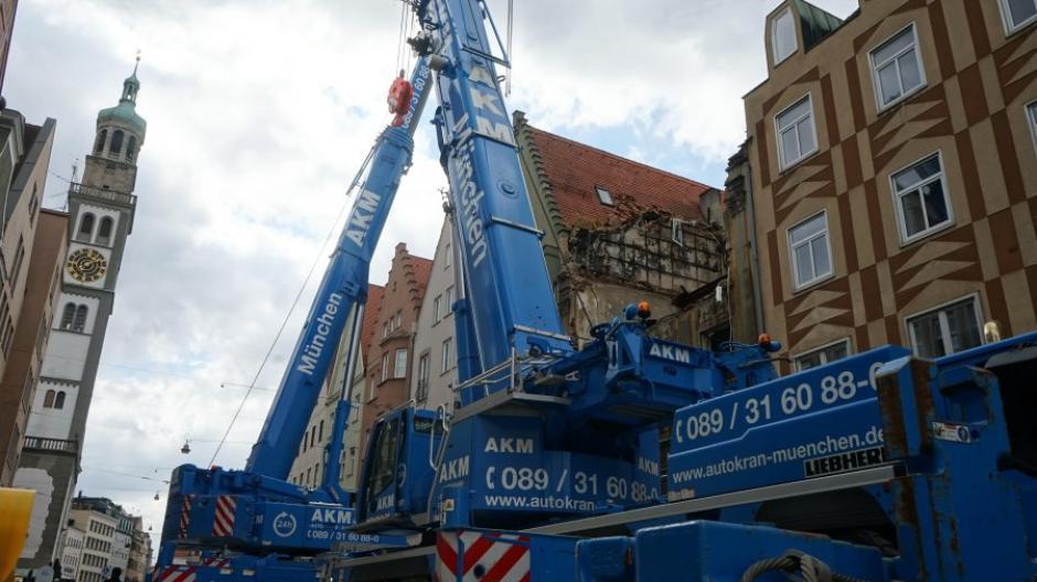 Zwei große Autokräne sind in der Karolinenstraße in Augsburg jetzt im Einsatz, um ein Nachbargebäude des Brandhauses zu sichern.