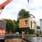 In Ursberg entsteht eine neue Kleinsthaus-Siedlung: Hier wird die erste Hälfte eines Holzhauses, das im Dominikus-Ringeisen-Werk gebaut wurde, auf das vorbereitete Fundament gestellt.