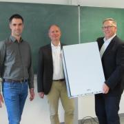 Schulleiter Andreas Eberle (rechts) vom St.-Thomas-Gymnasium präsentiert seinen Kollegen Christian Hörtrich (Mitte) und Josef Sumser das erste Luftfiltergerät.