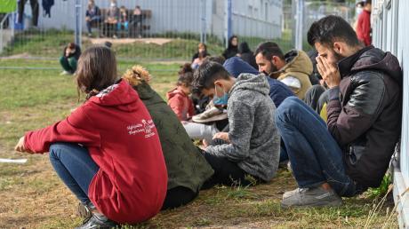 Mehrere Migranten sitzen auf einer Wiese vor Containern in der Zentralen Erstaufnahmeeinrichtung für Asylbewerber (ZABH) des Landes Brandenburg.
