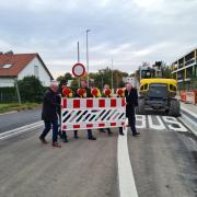 Die Neugestaltung des Verkehrsraums am Meringer Schulzentrum ist abgeschlossen und die Ambérieustraße wieder freigegeben. Bürgermeister Florian Mayer (rechts) und Landrat Klaus Metzger (links) tragen mit den Schulleiterinnen und Schulleitern den Absperrzaun weg.
